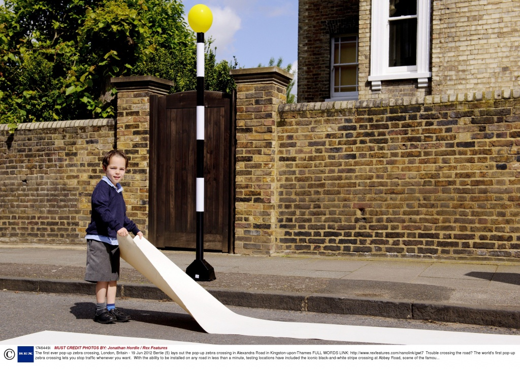 Mandatory Credit: Photo by Jonathan Hordle / Rex Features (1746449i) Bertie (5) lays out the pop-up zebra crossing in Alexandra Road in Kingston-upon-Thames The first ever pop-up zebra crossing, London, Britain - 19 Jun 2012 FULL WORDS LINK: http://www.rexfeatures.com/nanolink/gwt7 Trouble crossing the road? The world's first pop-up zebra crossing lets you stop traffic whenever you want. With the ability to be installed on any road in less than a minute, testing locations have included the iconic black-and-white stripe crossing at Abbey Road, scene of the famous Beatles album cover shoot, and a residental road in North London. The idea was developed by parents in Kingston-upon-Thames after their request for a safe crossing outside their children's school was turned down on the basis of cost; according to the Highways Agency, a basic zebra crossing costs an eye-watering GBP 114,000. The pop-up zebra crossing costs less than GBP 50 to install and uses recycled linoleum, drain pipes and two orange balloons to create an effect that is almost indistinguishable from the real thing.